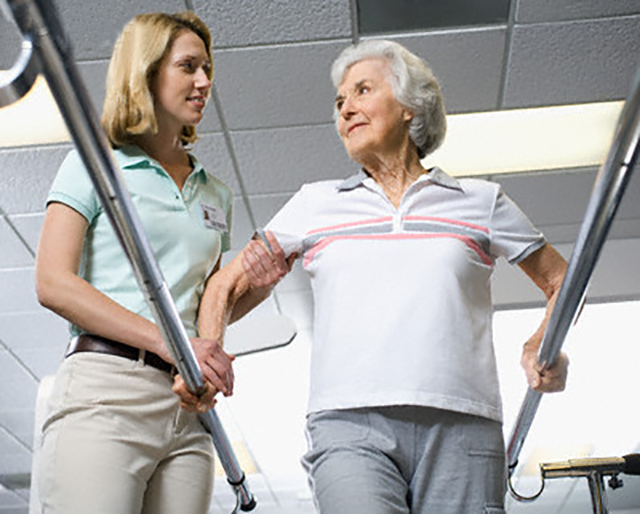 Physical Therapist Assisting Woman --- Image by © Simon Jarratt/Corbis